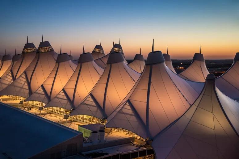 Необычная обтянутая тканью палатка (или типи) главного терминала аэропорта, спроектированная так, чтобы отражать близлежащие заснеженные Скалистые горы. Архитектура Tensil в международном аэропорту Денвера. Джордж Роуз / Getty Images (обрезано)